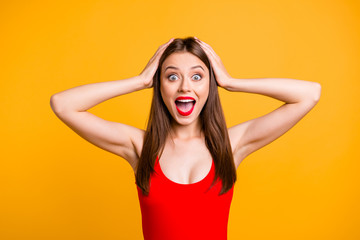 Close up portrait of  girl with a shocked face holds her head in her hands and can not believe in discounts on travel and journey to the sea isolated on vivid yellow background