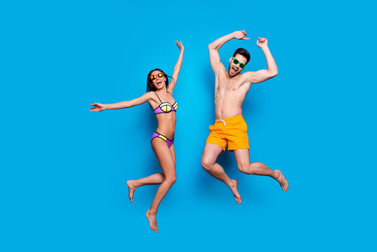 Full length portrait of a joyful young jumpers woman and happy man in sunglasses, dressed in swimsuit, jumping and putting hands up over blue background. Beach party style!