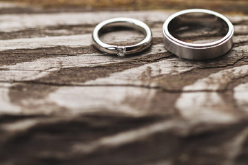 Jewelry shot of wedding rings on wooden texture with shadows of tropical leaves. Beautiful light