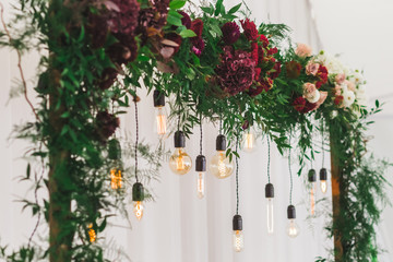 Wedding reception decoration with different electric edison lamps and fresh red and bordo flowers, rustic style