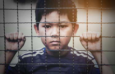 Dark portrait of a boy stand behind and holding steel screen or chain link fence - stressed sad child with no freedom concept