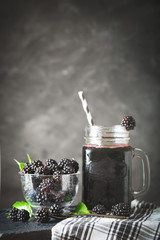 Ripe blackberry and blackberry juice on a wooden table. Dark background.