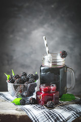 Ripe blackberry, blackberry juice and jam on a wooden table. Dark background.