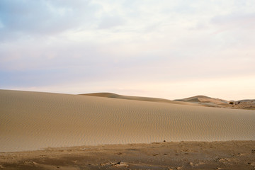 Scenic view of sandy dune hills at sunset