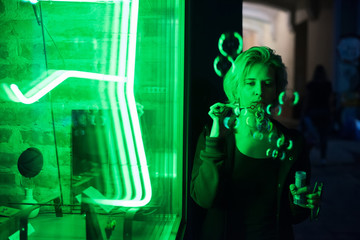 Night portrait of young blonde woman with soap bubble near green neon showcase. Art concept