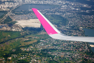 Wing of an airplane is flying above Kiev, Ukraine