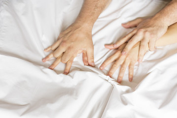 Couple having sex. Hand clutches grasps a white crumpled bed sheet in a hotel room, a sign of ecstasy, feeling of pleasure or orgasm