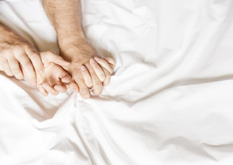 Couple having sex. Hand clutches grasps a white crumpled bed sheet in a hotel room, a sign of ecstasy, feeling of pleasure or orgasm Wall mural