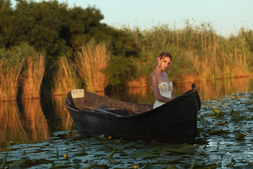 Beautiful young woman with elegant white dress posing in boat at sunset. Beautiful woman in authentic fishing boat getting maried.