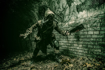 Post apocalyptic mutant creature or survivor in tatters and gas mask jumps out of darkness and attacking with handmade machete in abandoned tunnel, frightening dungeon or city old sewage collector Wall mural