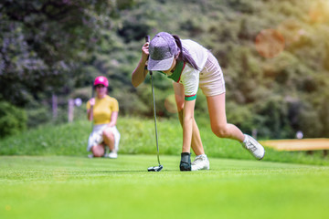 young woman golf player taking a golf ball in the hole on the green, with golfmate or challenger competitor exciting or enforcement in background, exciting or enforcement between players