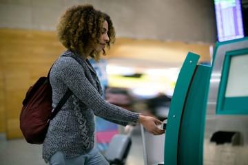 Woman using airline ticket machine