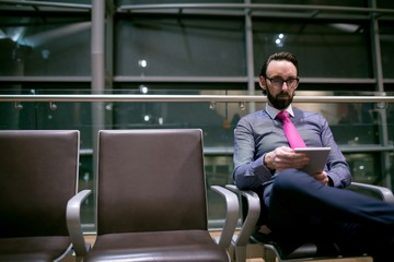 Businessman using digital tablet in waiting area