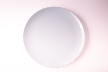 Top view of a pastel plate on a pastel peach background. Minimalism food photography. Geometric style. Copy space