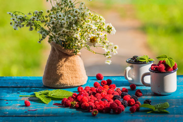 Ripe red raspberry and blackberry and garden flowers on old wooden table.