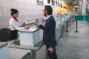 Airline check-in attendant handing digital tablet to commuter