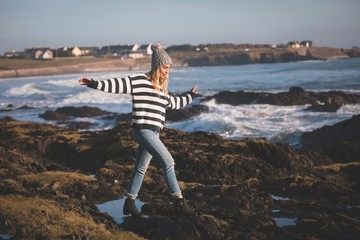 Woman walking with arms outstretched at beach