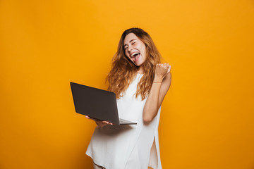 Portrait of a cheerful young girl holding laptop computer