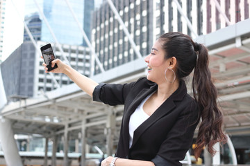 Attractive young Asian woman taking a photo or selfie with mobile smart phone on street of modern city.