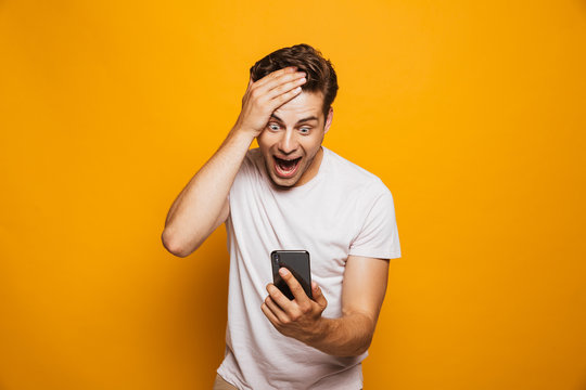 Portrait of a thrilled young man looking at mobile phone