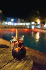 Sangria carafe on the wooden table at night by the pool