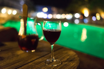 Glass of sangria on the wooden table at night by the pool