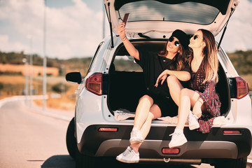 Two women taking selfie while sittink in a trunk. Road trip concept.