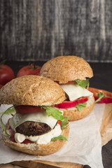Fresh homemade burgers on wooden serving board. Metall background, selective focus, copy space. Glass of soda.