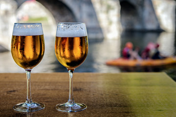Chilled glasses of beer on outdoors bar table with natural background; focus on drinks.