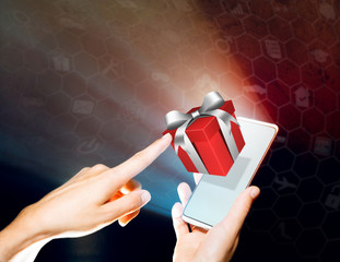Hands of a woman is holding a smartphone. She clicks on the gift. Concept of gift giving, choice of gifts.