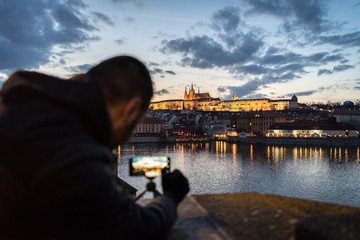 A man taking a night photo of Prague with his phone