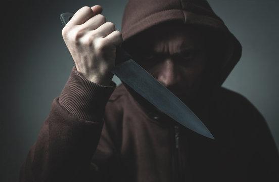 Criminal hooded man showing knife on dark room.
