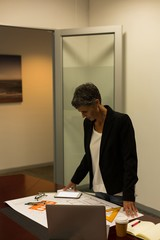Mature businesswoman checking construction diagram