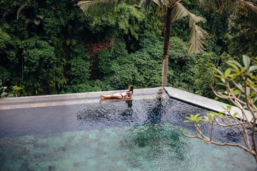 Slim sexy brunette woman in swimsuit relaxing on edge tropical infinity pool in jungle. Palms around and crystal clean water. Luxury resort on Bali island.