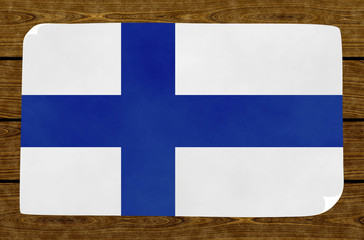 Illustration of a Finnish flag on the papier pasted on the woody wall