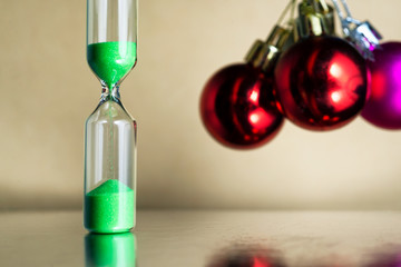 Modern beautiful green hourglass with christmas or xmas and new year balls.