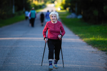 Nordic walking. An elderly woman with ski poles is on the road. Wall mural