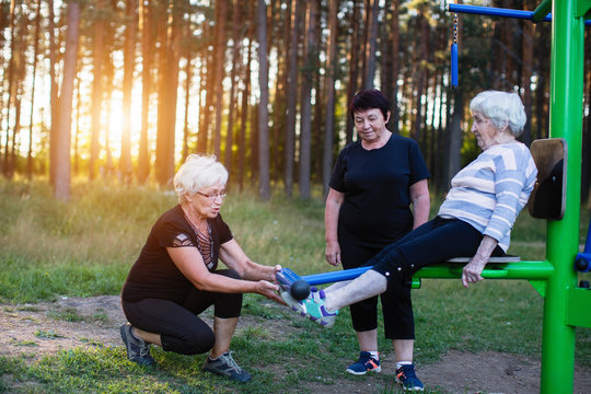 An elderly woman on a sports simulator in the Park, two adult women help her to do exercises. Health club and rehabilitation.