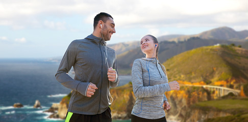 fitness, sport and technology concept - happy couple running and listening to music in earphones over bixby creek bridge on big sur coast of california background