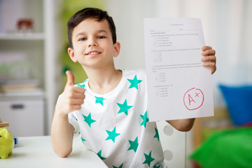 childhood, education and people concept - happy smiling boy holding school test with a grade...