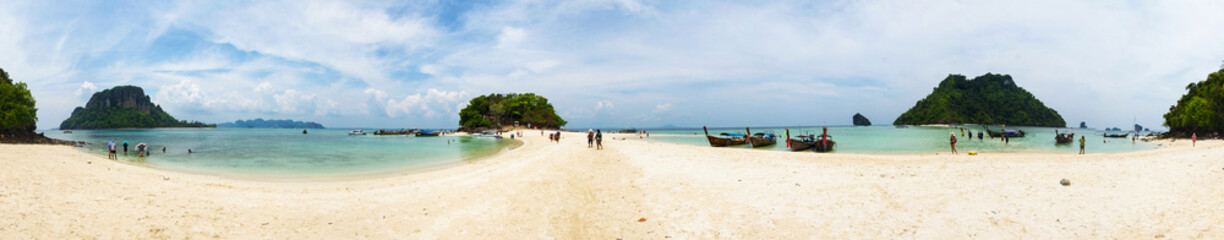 Panorama of Chicken Island tourist beach, with boats anchored and rock formations, Thailand