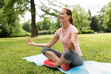 fitness, yoga and healthy lifestyle concept - happy woman meditating in summer park