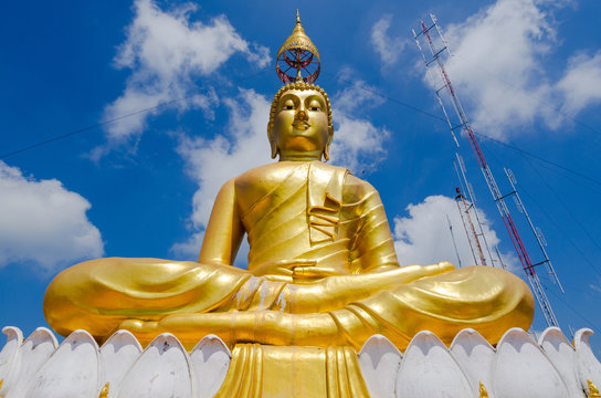 Monumental Buddha figure, gilded, with head umbrella, on top of Tiger rock near Krabi Thailand, and radion antenna in background.