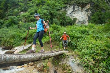 Woman walking across log with hiking poles in Nepal.