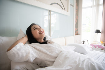 Cheerful woman wake up with fresh feeling in clean bedroom