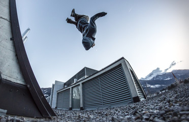 Young Parkour and Freerunning athlete performing a backflip on a roof
