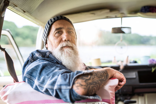 Portrait of an old hipster sitting in a van looking at camera