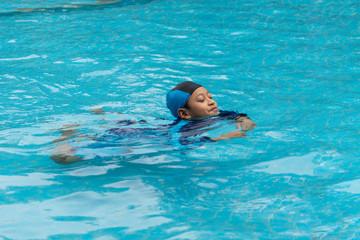 Foto op Canvas Dolfijnen Portrait of a boy playing in public swimming pool