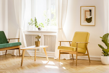 Yellow, retro armchair and a green sofa by a big, sunny window in a stylish, white real living room interior with a poster on the wall