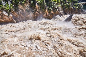 Turbulent muddy mountain river, Tiger Leaping Gorge, China.